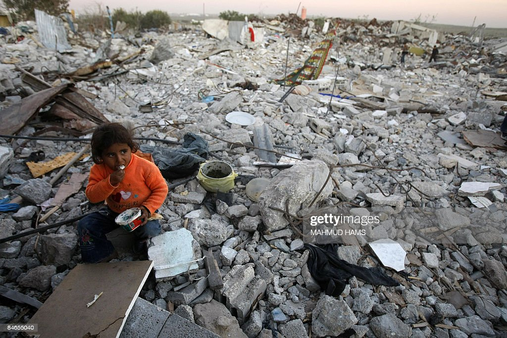 A Palestinian girl eats as she sits on the rubble of houses that were destroyed during Israel�s 22day offensive in the Gaza Strip on February 4 2009...