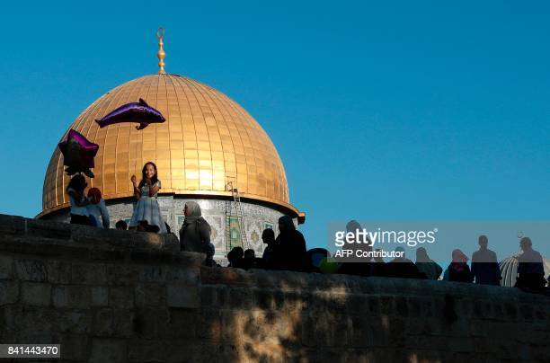 A Palestinian girl flies a helium balloon shaped like a dolphin as others sit on a wall overlooking the Dome of the Rock inside alAqsa Mosque...