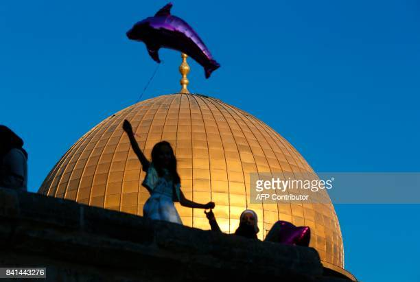 A Palestinian girl flies a helium balloon shaped like a dolphin by the Dome of the Rock inside alAqsa Mosque compound in Jerusalem's old city on the...