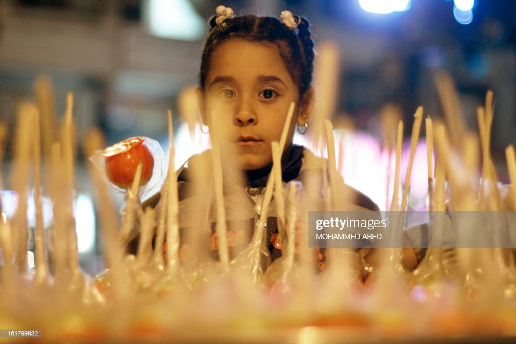 A Palestinian girl holds a candy apple in Gaza City on February 16, 2013. The European Union called on Israel to respect its human rights obligations towards Palestinian prisoners, saying it was concerned about the condition of four detainees on a long-term hunger strike. AFP PHOTO/MOHAMMED ABED