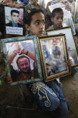 A Palestinian girl holds a picture of a relative and of jailed Fatah leader Marwan Barghuti during a protest at the Red Cross offices in Gaza City...