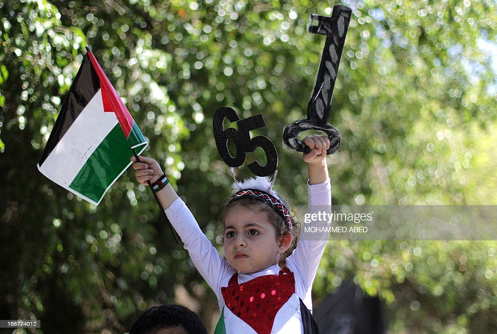 A Palestinian girl holds a replica of a house key, representing the front door key of am abandoned home, as she attends the 65th Nakba day or 'Day of Catastrophe' rally in Gaza City, on May 15, 2013. Palestinians and Arab Israelis are marking what to them is the Nakba -- Arabic for 'catastrophe' -- of the creation of the Jewish state and exodus of 760,000 of them from their homes in 1948.