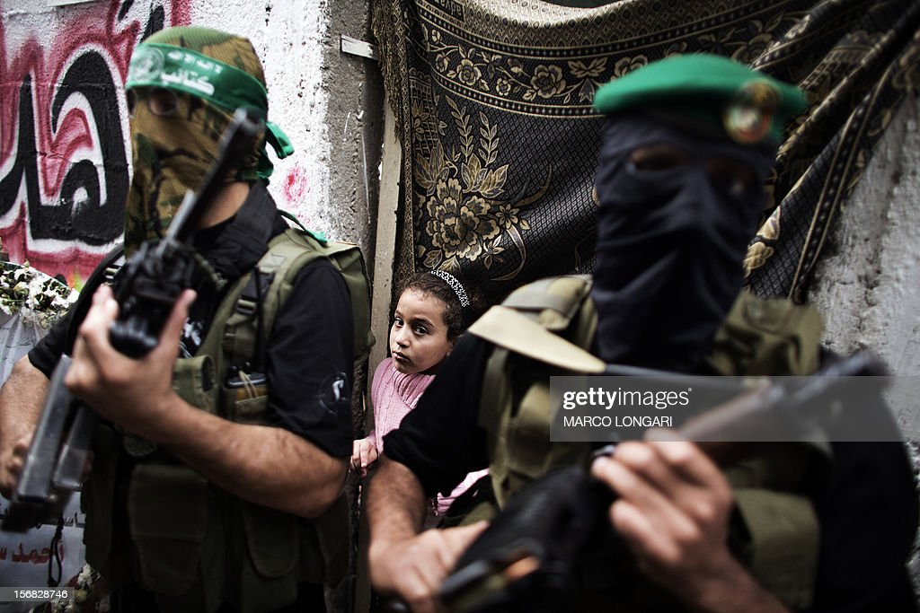 A Palestinian girl is seen behind gunmen from the Ezzedine al-Qassam Brigades, the armed wing of Hamas, as they line up outside the house of their late leader Ahmed Jaabari, while mourners visit his family to pay their condolences in Gaza City on November 22, 2012. Israeli politicians returned to the campaign trail as the streets of Gaza came back to life after a truce ended eight days of bloodshed, with both sides claiming victory while remaining wary.