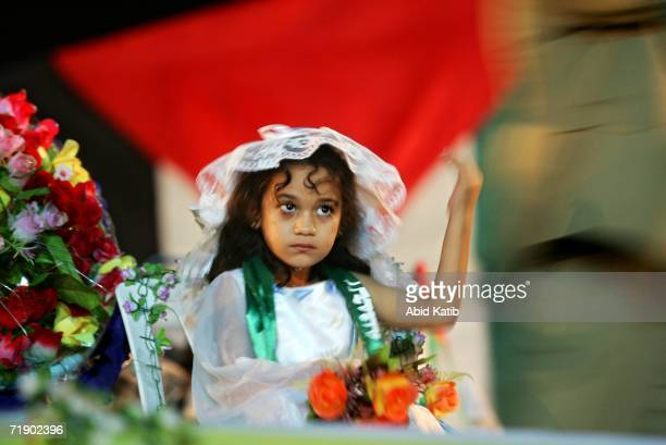 Palestinian girl is seen wearing a bride's veil as she attends a mass wedding party organized by the ruling Islamist group's charity organization for...