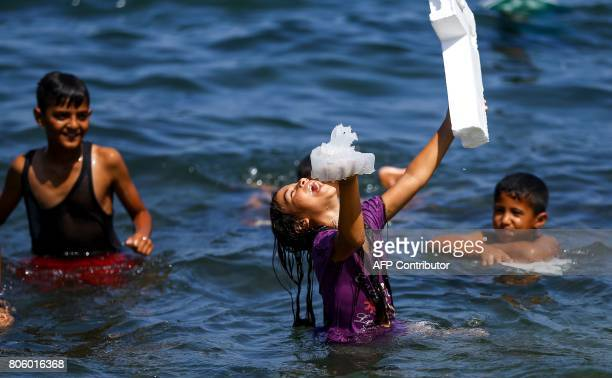 A Palestinian girl laughs while holding a jellyfish in one hand a block of foam in another as she stands in the Mediterranean sea near alShati...