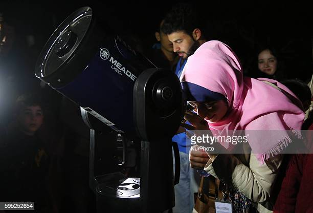 A Palestinian Girl look through a telescope to watch the moon and stars at Alqattan center in Gaza city on March 23 2016