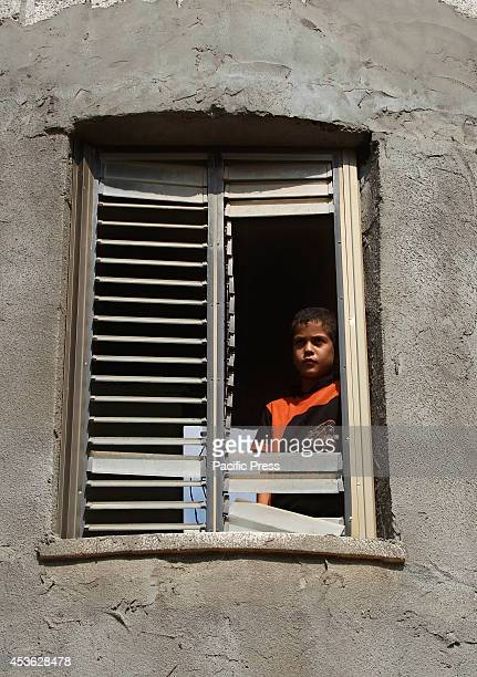 Palestinian girl looks outside from their damage window from an Israeli air strike in some parts of Khan Younis in the Southern of Gaza City...