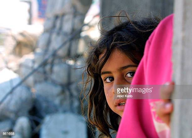 Palestinian girl peers out from the remains of her house destroyed by Israeli bulldozers June 26 2002 in Rafah Gaza Strip near the border with Egypt...