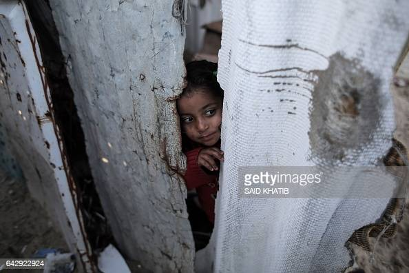 Palestinian girl peers through the door of her house in an impoverished area in the southern Gaza Strip town of Khan Yunis on February 19 2017 / AFP...