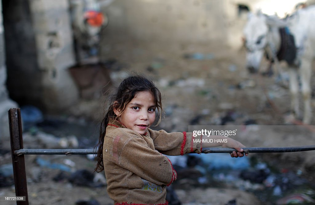 A Palestinian girl poses for a picture in a poverty-stricken quarter of the town of Beit Lahia, in the northern Gaza Strip, on April 28.2013. AFP PHOTO/MAHMUD HAMS