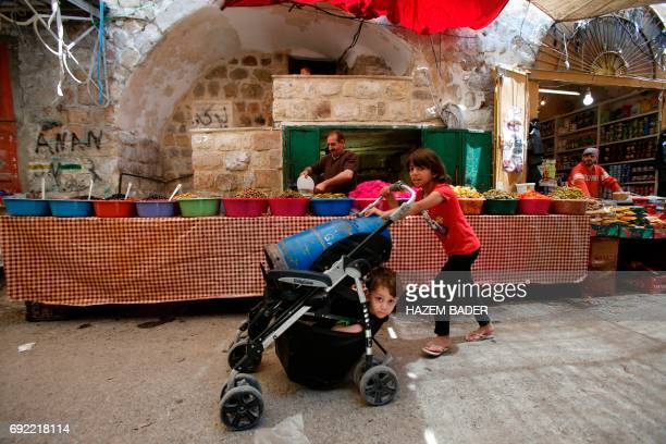 A Palestinian girl pushes a pram carrying her brother and a oil canister past a stall of pickles for sale in the old city of the West Bank town of...
