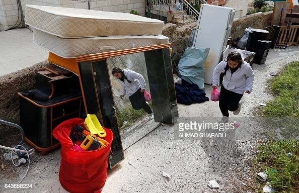 A Palestinian girl runs past the belongings of the Abu Ramouz house that was demolished by Israeli army bulldozers in the Arab east Jerusalem...