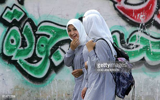 Palestinian girl shares a laugh with friends as they walk back home from school passing a wall with graffiti praising a 'martyr' in the northern Gaza...