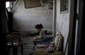 A Palestinian girl sits and eats in the rubble of her destroyed home on August 2 2014 following an overnight Israeli strike on Gaza City A fresh wave...