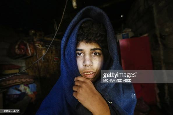 A Palestinian girl sits wrapped in a blanket in her home a hovel amid poor living conditions in the Jabalia refugee camp in the northern Gaza Strip...