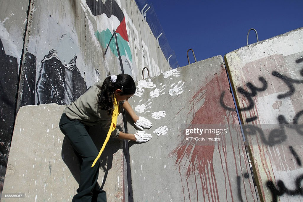 A Palestinian girl stamps her hand prints on the Israeli built controversial separation barrier at the main entrance of the West Bank town of Bethlehem, as she and others take part in the 'Project Peace on Earth' activity to send out a message of peace on New Year's eve, December 31, 2012.