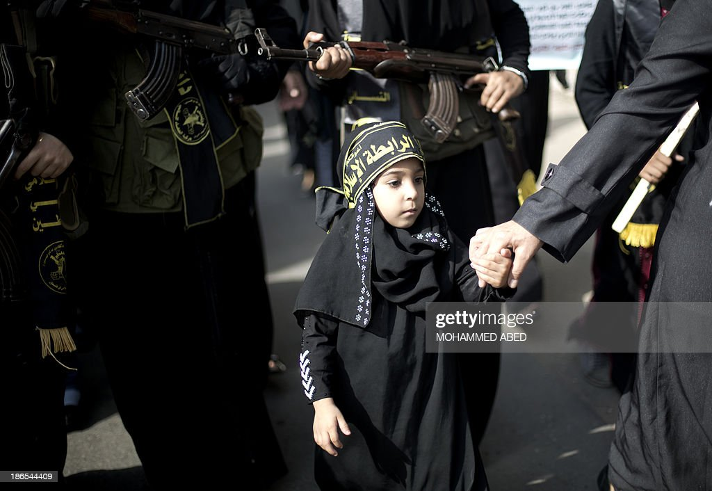 A Palestinian girl stands with women holding assult rifles as they take part in a rally by the Islamic Jihad to mark the anniversary of the movement's foundation in Gaza City, on November 1, 2013. AFP PHOTO/MOHAMMED ABED
