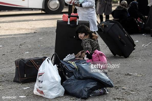 A Palestinian girl waits with her family for travel permits to cross into Egypt through the Rafah border crossing after it was opened by Egyptian...