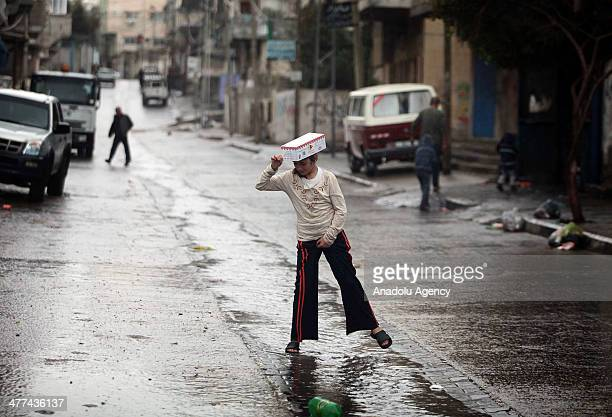 Palestinian girl walks at a street during a rainy day at AlShati refugee camp in Gaza City Gaza on March 09 2014 Heavy rain affects the daily life...