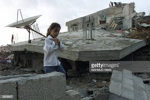 A Palestinian girl walks in front of the a destroyed house attacked by the Israeli army in Nuseirat refugee camp in the Gaza Strip 18 September 2003...