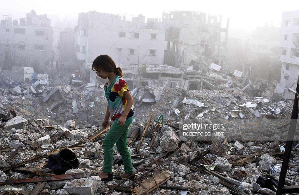 A Palestinian girl walks on the rubble strewn cieling of her family's home after she and other members of her family returned to their partially...