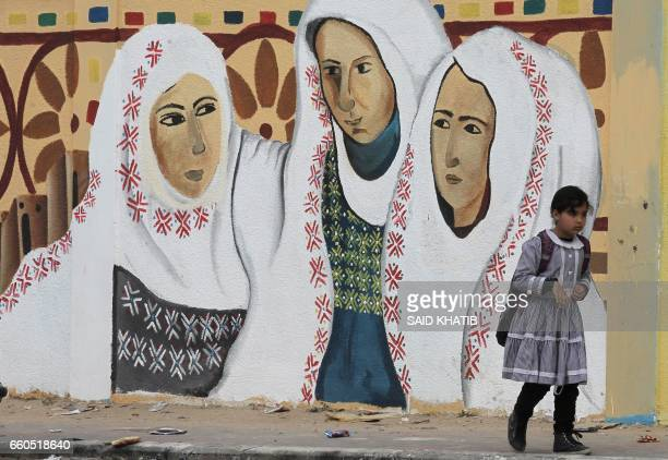 Palestinian girl walks past a mural on a street in Rafah in the southern Gaza Strip on March 30 which marks Land Day Land Day marks the killing of...