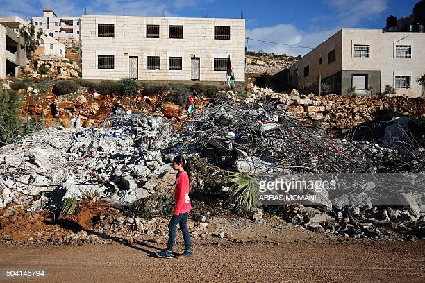 A Palestinian girl walks past the family home of Muhanad Halabi who killed two Israelis and wounded two more including a toddler in a knife and gun...