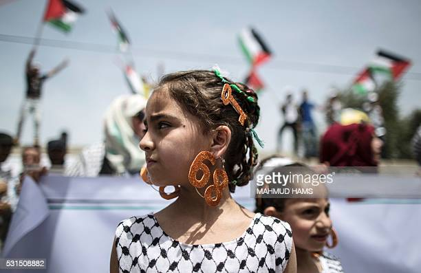 Palestinian girl wears earrings bearing the number '68' and a hair slide in the shape of a key on May 15 2016 in Gaza city during a rally to...
