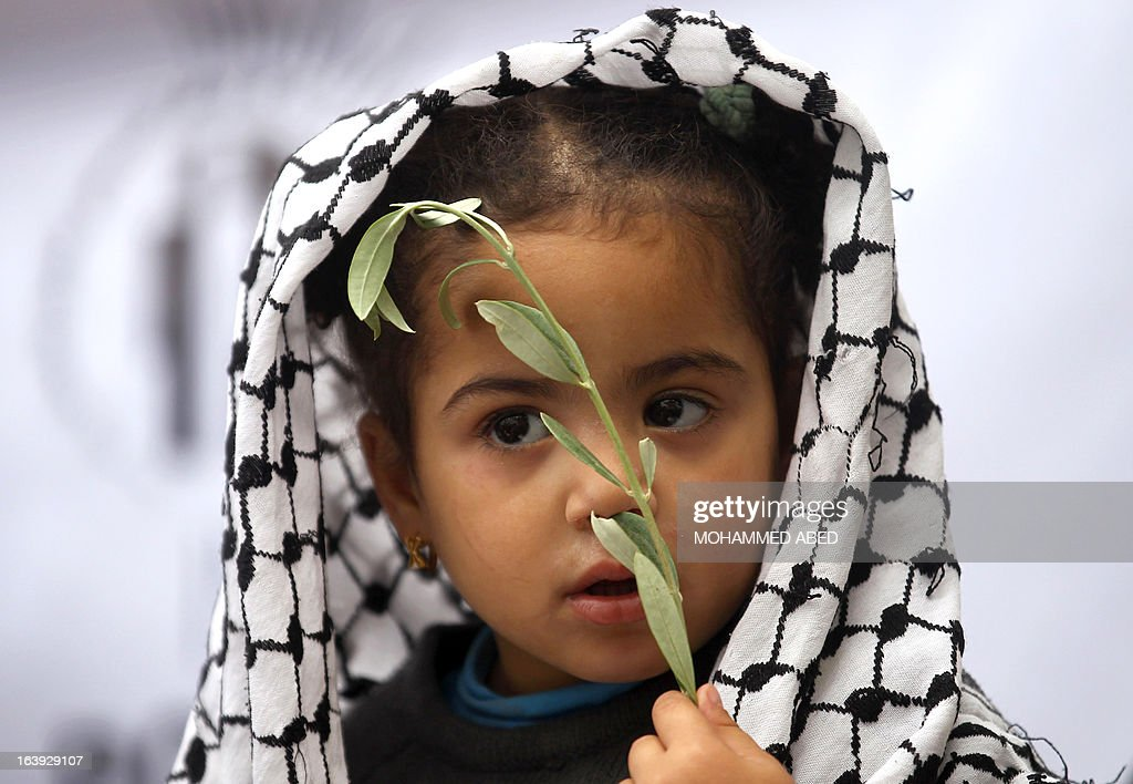 A Palestinian girl with a traditional Arab Keffiyeh scrave on her head holds an olive branch during a protest calling for the release of Palestinian prisoners being held in Israeli jails outside the Red Cross offices in Gaza City on March 18, 2013.