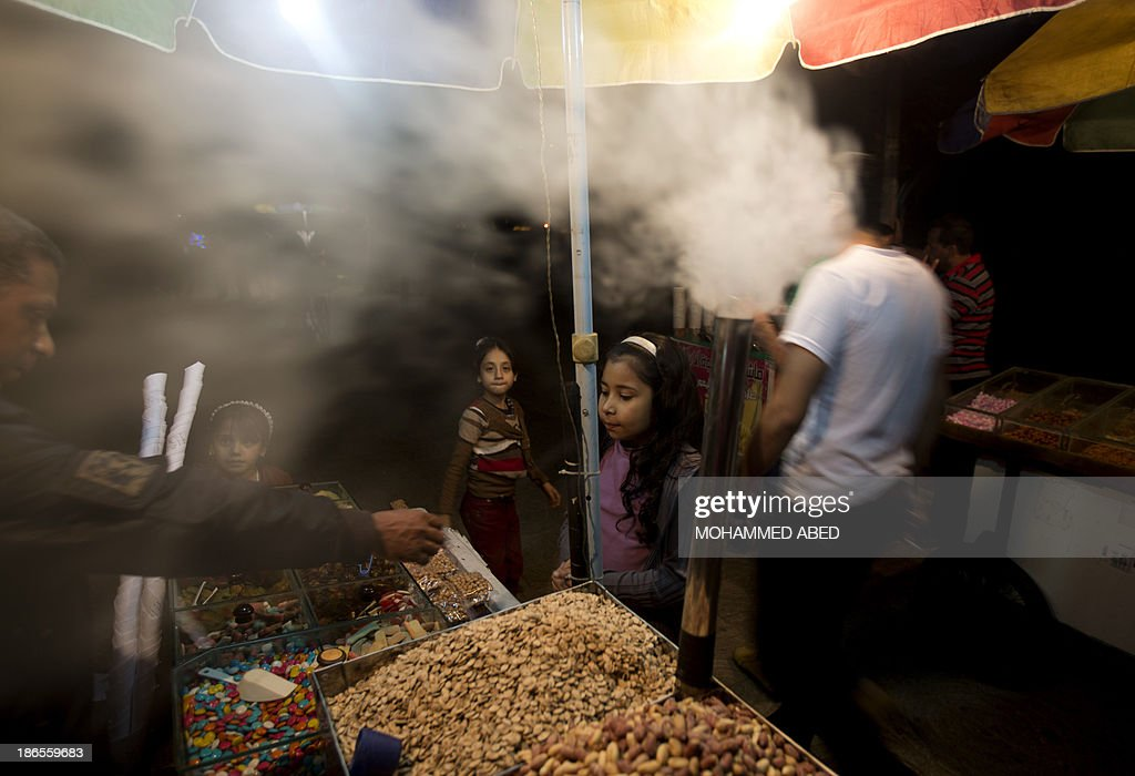 Palestinian girls buy from a street vendor using a power generator to make up for the power outage in Gaza City, on November 1, 2013. A shortage of fuel halted the production of electricity across the Gaza Strip, said the energy authority of the Islamist movement Hamas, which controls the Palestinian enclave.