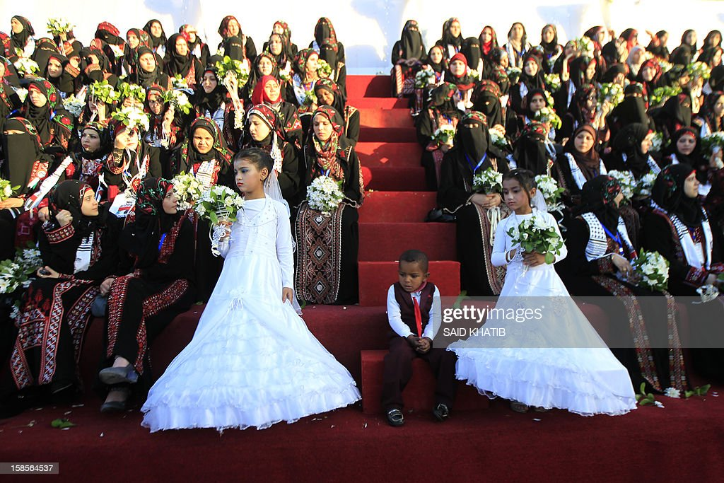 Palestinian girls (Front L-R), dressed as bridesmaids, stand in front of brides during a mass wedding ceremony in Rafah, southern Gaza Strip, on December 19, 2012. Some 436 couples in need participated to the mass wedding organized by the National Islamic Committee in the Gaza Strip and other financial donations.