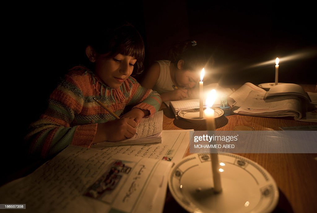 Palestinian girls finish their homework using candle light to make up for the power outage in Gaza City, on November 1, 2013. A shortage of fuel halted the production of electricity across the Gaza Strip, said the energy authority of the Islamist movement Hamas, which controls the Palestinian enclave.