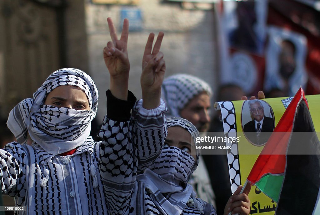 Palestinian girls flash the 'V' for victory sign during a protest calling for the release of Palestinian prisoners from Israeli jails outside the International Red Cross offices in Gaza City on January 21, 2013.
