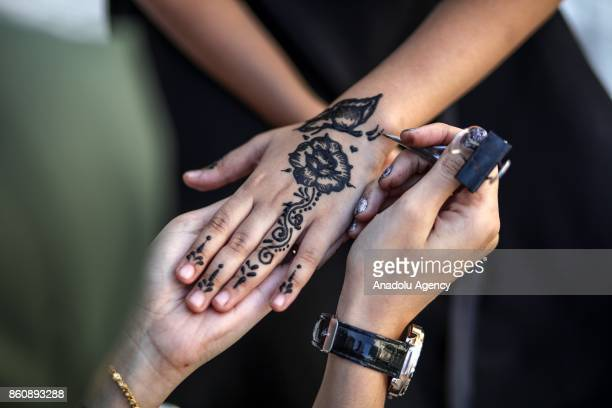 Palestinian girls have their hands decorated with henna in Gaza City Gaza on October 13 2017 The tradition of henna painting has resurfaced among...