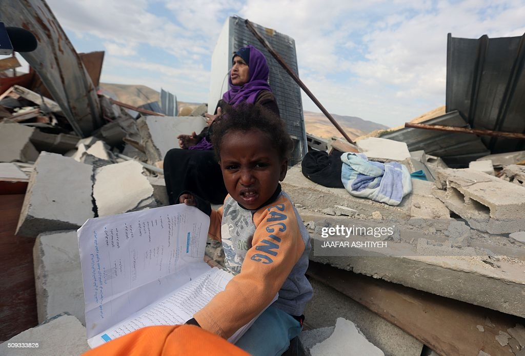 A Palestinian girls hold a book as she sits on the rubble of her house after it was demolished by Israeli authorities on February 10, 2016 in the West Bank village of Jeftlek, in the Jordan valley near Jericho. Israel often demolishes buildings constructed without the required Israeli permits in Area C of the West Bank, which is under full Israeli control. / AFP / JAAFAR ASHTIYEH