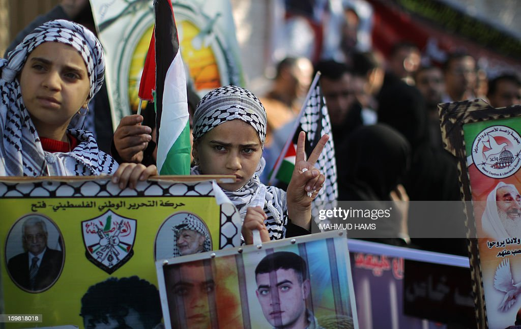 Palestinian girls hold pictures of relatives improvised in Israeli jails during a protest calling for prisoners' release outside the International Red Cross offices in Gaza City on January 21, 2013 .