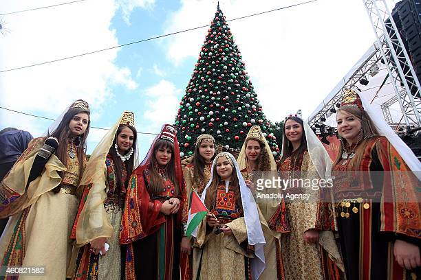 Palestinian girls in traditional clothes pose in front of a Christmas tree at Manger Square in Bethlehem West Bank on December 24 2014