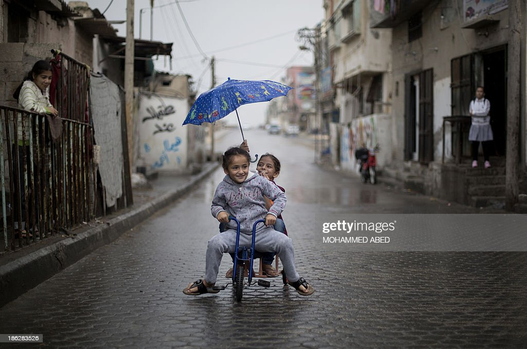 Palestinian girls play in a street of al-Shatee refugee camp in Gaza City on October 30, 2013.