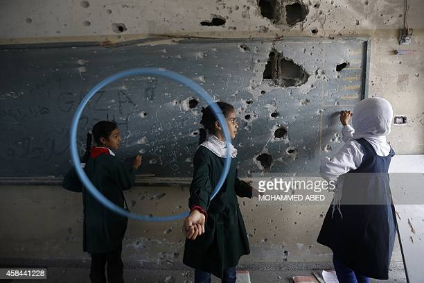 Palestinian girls play inside their school which was destroyed during the 50 days of conflict between Israel and Hamas last summer in the Shejaiya...