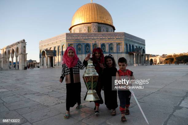 Palestinian girls pose for a picture with a Ramadan lantern in front of the Dome of the Rock at the AlAqsa Mosque compound in the Old City of...