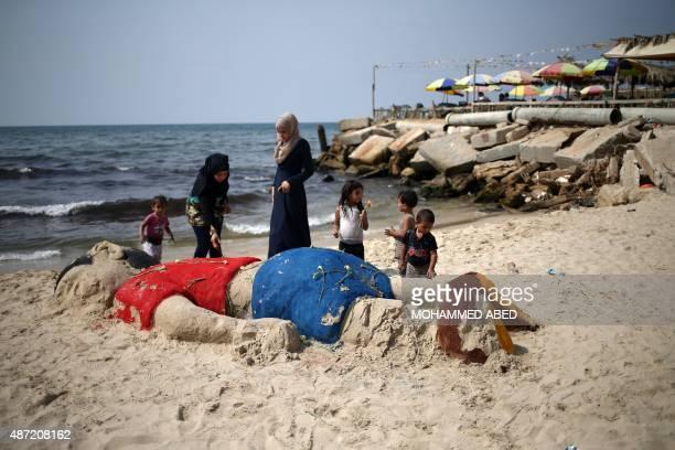 Palestinian girls put flowers on a sand sculpture depicting Syrian boy Aylan Kurdi a threeyearold boy who drowned off Turkey on September 7 on Gaza...