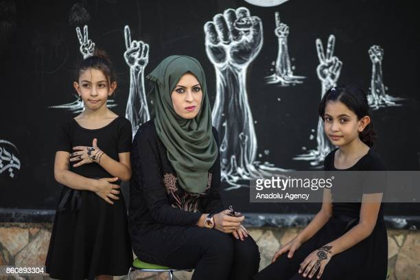 Palestinian girls show their hands decorated with henna in Gaza City Gaza on October 13 2017 The tradition of henna painting has resurfaced among...