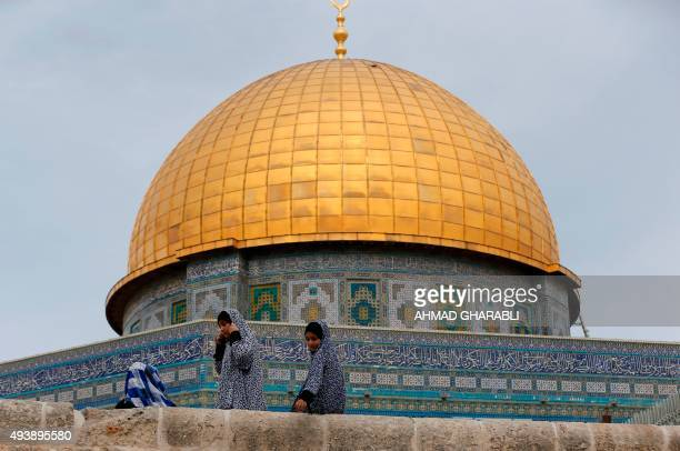 Palestinian girls sit in front of the Dome of the Rock at the AlAqsa Mosque compound in Jerusalem before the Friday prayer on October 23 2015 Earlier...