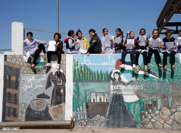 TOPSHOT Palestinian girls sit on a wall at the Dalal alMughrabi elementary school on October 12 in the village of Beit Awwa west of the West Bank...