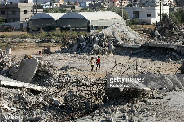 Palestinian girls walk between the rubble of houses which destroyed during the 50day Israeli war against Gaza in the summer of 2014 in the village of...