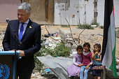 Palestinian girls watch Belgian Foreign Minister Didier Reynders deliver a speech in the eastern Gaza City Shujaiya neighbourhood which was destroyed...