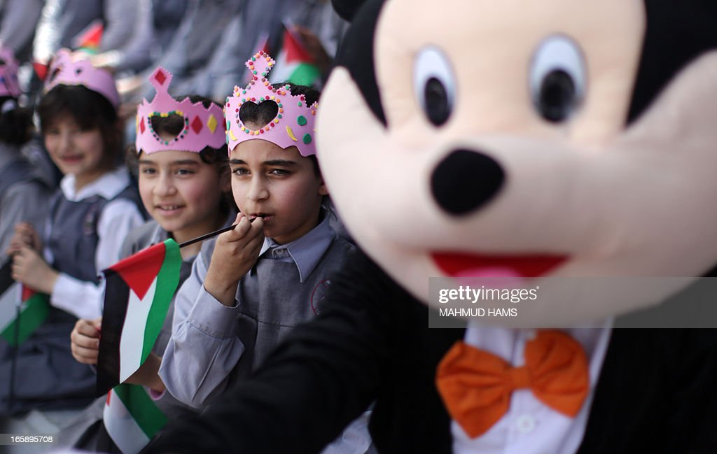 Palestinian girls wear crowns near a Mickey Mouse puppet during the Children's Fund festival at the Community College of the Islamic University of Gaza in Gaza city on April 7, 2013.