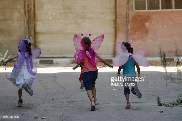Palestinian girls wearing costumes play in the besieged Yarmuk refugee camp in the Syrian capital Damascus on August 31 2015 Several thousand...