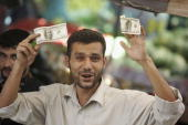 Palestinian government employee holds cash that he received as part of his salary at a post office June 19 2006 in Gaza City Gaza Strip Days after...