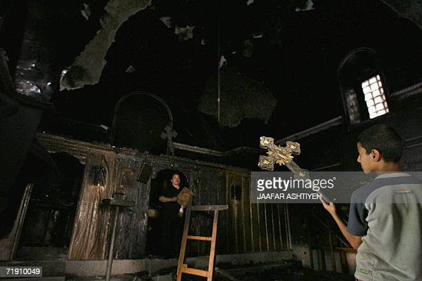 Palestinian Greek Orthodox worshippers rescue items form their badly damaged church in the northern West Bank town of Tulkarem 17 September 2006 The...